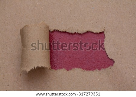 Torn brown color paper with space for text with red background - stock photo