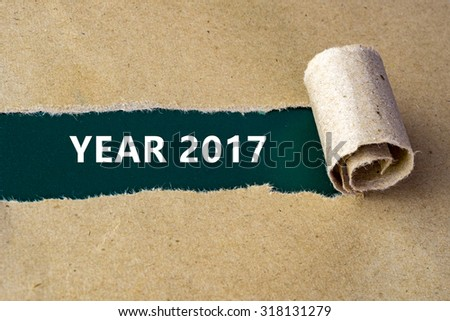 "Torn brown paper on green surface with ""YEAR 2017"" words."