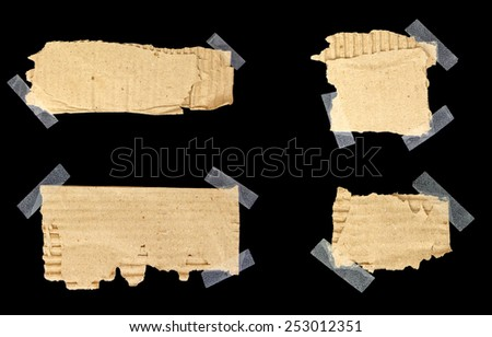 Torn cardboard scraps stuck with scotch tape with copy-space isolated on black - stock photo