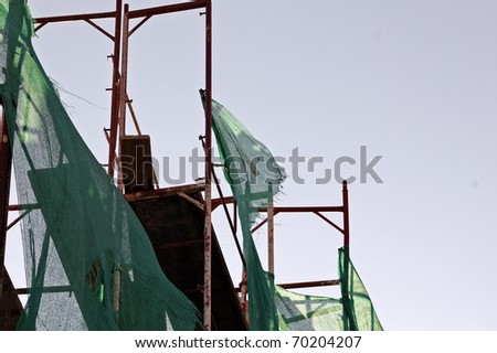 Torn debris netting and scaffold at construction site.