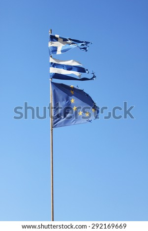 Torn Greek flag and torn European Union flag on blue background - stock photo