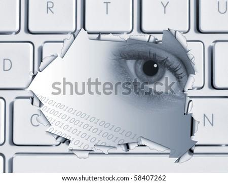 Torn hole in computer keyboard revealing watching eye - stock photo