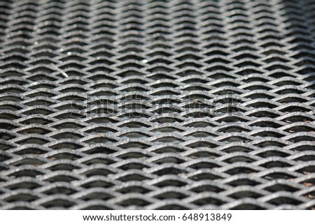 Torn metal mesh is used as a fence or wall.