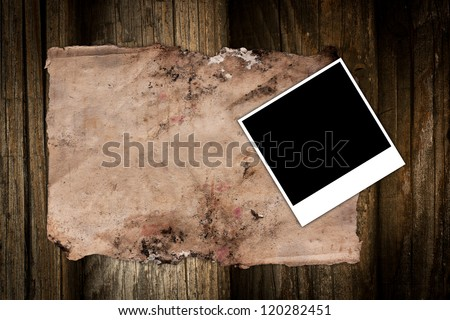 Torn old paper and photo frame on a wooden background