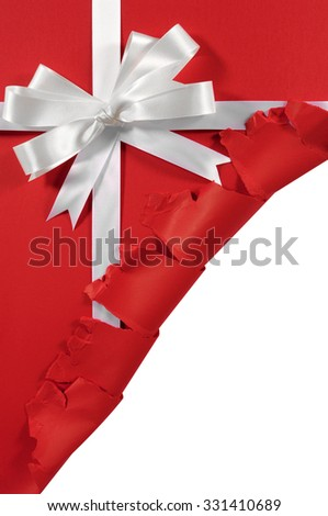 Torn open Christmas gift, white ribbon bow, red paper background, copy space, vertical - stock photo
