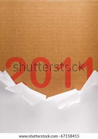 Torn packaging paper revealing 2011 written on brown cardboard box - brand new year concept - stock photo