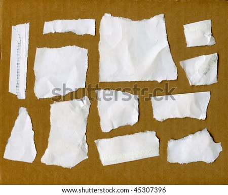 Torn Paper Scraps On Cardboard Wall - stock photo