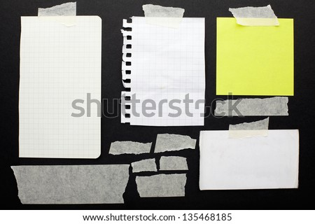 Torn paper scraps set and tape on black background with clipping path - stock photo