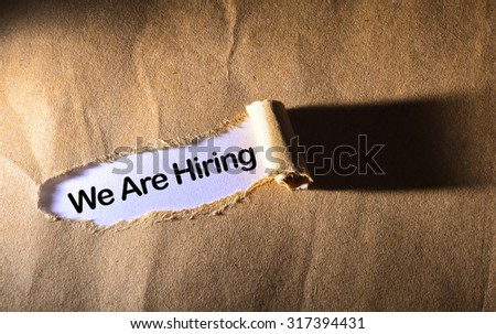torn paper with word We Are Hiring - stock photo