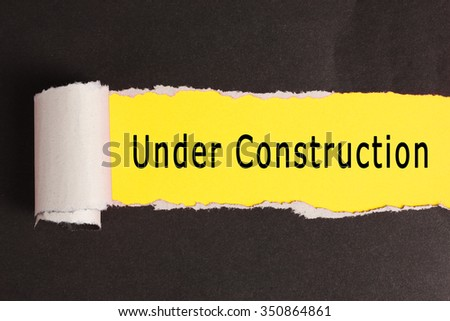 Torn paper with yellow background and text Under Construction - stock photo