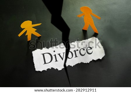torn piece of paper with divorce text and paper couple figures - stock photo