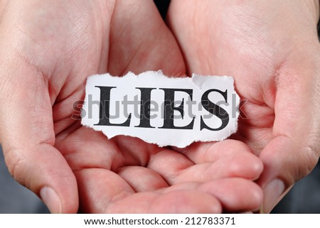 "Torn piece of paper with the word ""Lies"" in the palms. Close-up."