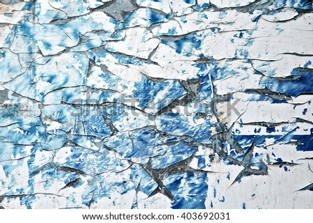 Torn poster wall. Old advertisement peeling blue background. Art billboard on street. Close up. - stock photo