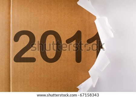 Torn wrapping paper revealing 2011 written on brown cardboard layer - new year concept - stock photo