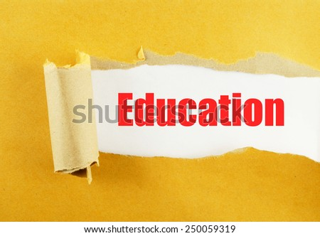 Torn yellow paper with word education on white background  - stock photo