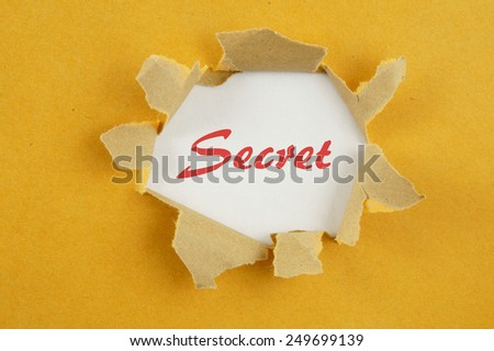 Torn yellow paper with word secret on white background  - stock photo
