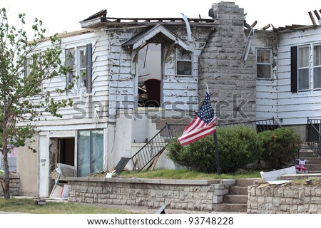 Tornado damaged home with American Flag.  Nationwide, many who's homes suffer horrific damage by powerful tornadoes, fly flags as a symbol of hope and of triumph over adversity! - stock photo