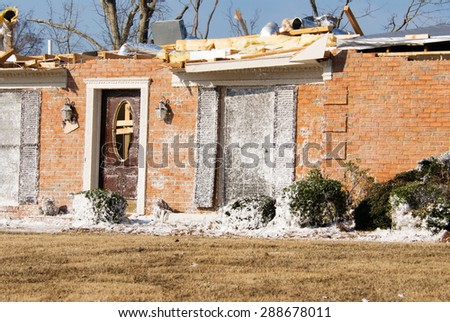Tornado destroyed brick house with white insulation debris on the exterior surface. Roof has been ripped off and the house has been boarded up. Selective focus on the house near the door and windows. - stock photo