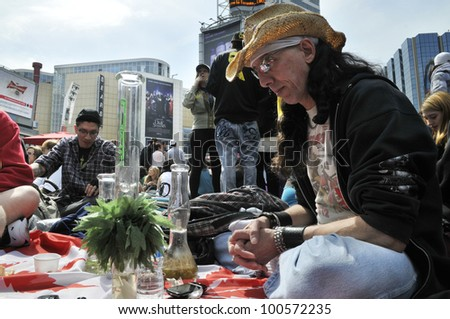 TORONTO - APRIL 20:  A marijuana activist sitting in front of his bong  during the annual marijuana 420 event at Yonge & Dundas Square  on April 20  2012 in Toronto, Canada. - stock photo