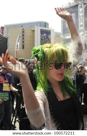 TORONTO - APRIL 20: A marijuana legalization activist dressed all in green dancing   during the annual marijuana 420 event at Yonge & Dundas Square  on April 20  2012 in Toronto, Canada. - stock photo