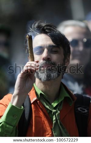 TORONTO - APRIL 20: A marijuana legalization activist smoking marijuana during the annual marijuana 420 event at Yonge & Dundas Square  on April 20  2012 in Toronto, Canada. - stock photo