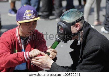 TORONTO - APRIL 20:   A marijuana smoker helping his friend  tolight a bong during the annual marijuana 420 event at Yonge & Dundas Square  on April 20  2012 in Toronto, Canada. - stock photo