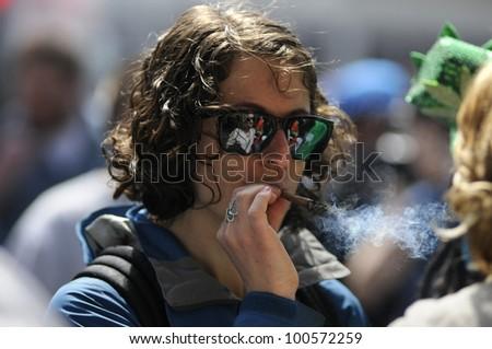 TORONTO - APRIL 20:  A marijuana smoking during the annual marijuana 420 event at Yonge & Dundas Square  on April 20  2012 in Toronto, Canada. - stock photo