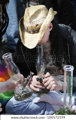 TORONTO - APRIL 20:  A middle aged man smoking  marijuana during the annual marijuana 420 event at Yonge & Dundas Square  on April 20  2012 in Toronto, Canada. - stock photo