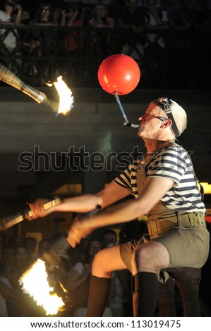 TORONTO-AUGUST 24:  A street performer juggling with fire during the Buskerfest Festival on August 24, 2012 in Toronto, Canada. - stock photo