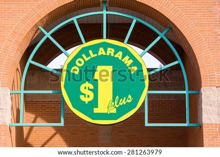 TORONTO,CANADA-APRIL 14,2015: The Dollarama sign board on a arch shaped metal frame, Dollarama is Montreal based and is Canada's largest retailer of items for three dollars or less - stock photo