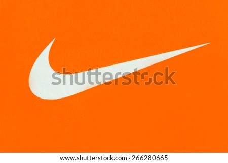 TORONTO,CANADA-APRIL 2,2015: White Nike Logo over orange background. Nike, Inc. is an American multinational corporation that designs, develops, manufactures and sells footwear and other items - stock photo