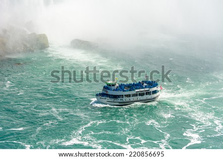 TORONTO,CANADA-AUGU ST 21, 2014: Maid of the mist boat taking tourists to the Horseshoe fall in the Niagara River. The boat starts in calm part of the River and takes its passengers to the falls. - stock photo