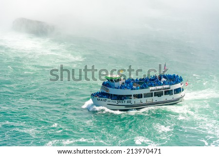 TORONTO,CANADA-AUGUST 21, 2014: Maid of the mist boat taking tourists to the Horseshoe fall in the Niagara River. The boat starts in calm part of the  River and takes its passengers to the falls. - stock photo