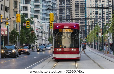 TORONTO,CANADA-AUGUST 12,2015: New Toronto street cars Flexity Outlook in evening street. The old streetcars are being phased out by the Bombardier Flexity Outlook.City transportation streetcar. - stock photo