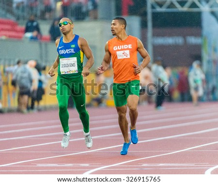 TORONTO,CANADA-AUGUST 8,2015: visually challenged Brazillian athlete running the race with the help of his guide at the 2015 Parapan American Games.