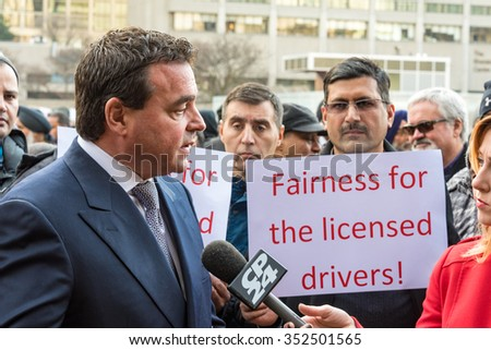 TORONTO,CANADA-DECEMBER 9,2015: Councillor Giorgio Mammoliti (in suit) addressed the angry crowd of taxi drivers protesting against the unfair operation of UberX outside City Hall. - stock photo