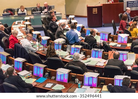 TORONTO,CANADA-DECEMBER 9,2015: Municipal government or city council working inside Toronto City Hall while taxi drivers watch the deliberation as part of the protest rally against UberX - stock photo