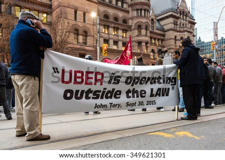 TORONTO,CANADA-DECEMBER 9,2015:Taxi drivers strongly protested the Uber operating illegally in the city. Drivers face unfair competition and the city has not enforced the bylaws for Uber - stock photo