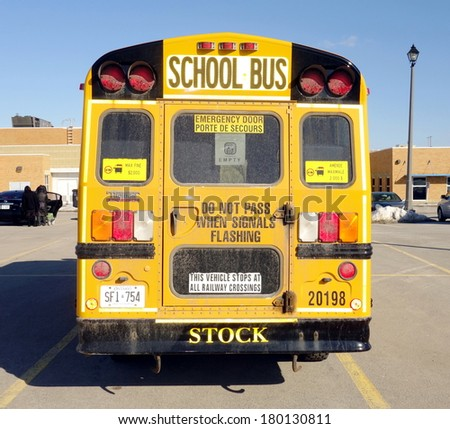 TORONTO, CANADA - FEBRUARY 23, 2014: A school bus parked in front of a school outside Toronto, Canada.