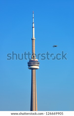 TORONTO, CANADA - JULY 2: Airplane and CN Tower on July 2, 2012 in Toronto. Buit in 1976 as the unique landmark of Toronto, it was world's tallest tower for 34 years - stock photo