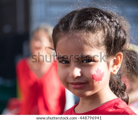 TORONTO,CANADA-JULY 1,2016:Canada Day people: child girl with red maple leaf painted on  her face..Canada Day  is the national day of Canada and a federal statutory holiday - stock photo