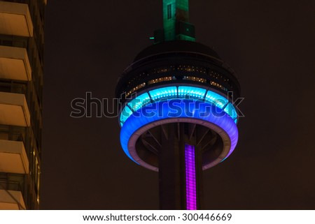 TORONTO,CANADA-JULY 2,2015:CN tower light trials for the Panam Games.  The observation deck of the tower glows blue, purple, and cyan.  Another building can be seen to the left side of the frame. - stock photo