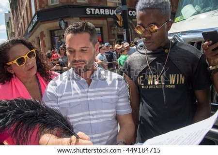 TORONTO,CANADA-JULY 3,2016:Mathieu Chantelois (gray stripes), Pride Toronto's executive director, signs a list of demands from Black Lives Matter which interrupted the parade for about 30 minutes.