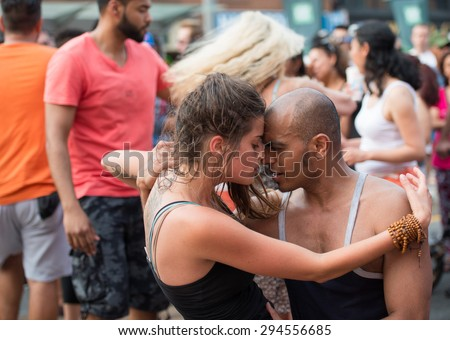 TORONTO,CANADA-JULY 5,2015: Sensual dance by multi racial couple in Salsa on St. Clair Ave West is the largest Hispanic festival in Canada gathering thousands every year. - stock photo