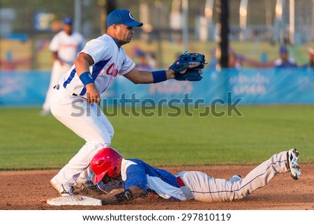 TORONTO,CANADA-JULY 14,2015:Toronto Pan American Baseball Games 2015: Yeixon Ruiz (Dominican Republic) arrives safe where Cuban short stop Yorbis Borroto  catches.Cuba won the game 9 to 5. CN 01953074 - stock photo