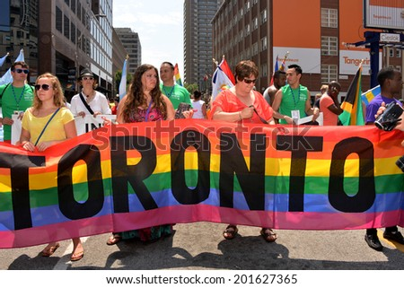 TORONTO, CANADA - JUN 29:   WorldPride parade participants hold the banner for the parade in the first North American city to host the event June 29, 2014 in Toronto, Ontario. - stock photo