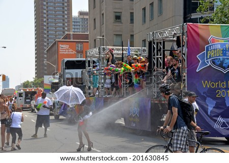 TORONTO, CANADA - JUN 29:   WorldPride participant gladly accepts the spray of water from a hose during the heat during the fnal parade June 29, 2014 in Toronto, Ontario - stock photo