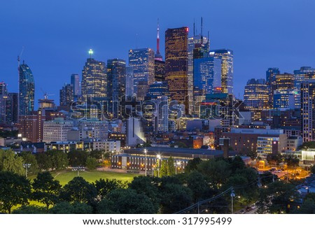 TORONTO, CANADA - JUNE 26, 2015: A night view from a high-rise building of  Moss Park Arena with nearby buildings,Toronto's Financial District skyscrapers and CN Tower apex at the background. - stock photo
