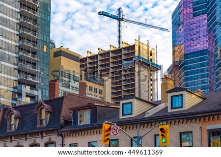 TORONTO,CANADA-JUNE 24,2016: Construction boom in real estate market. The housing market is hot in Toronto provoking a construction boom in the city. Construction crane next to the building.