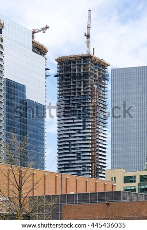 TORONTO,CANADA-JUNE 16,2016: Contruction boom in real estate market. The housing market is hot in Toronto provoking a construction boom in the city. Construction crane next to the building.